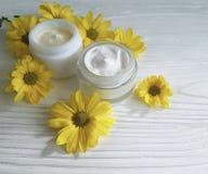 La margherita gialla cosmetica crema fiorisce il bello rilassamento del contenitore fatto a mano su un fondo di legno bianco Fotografia Stock