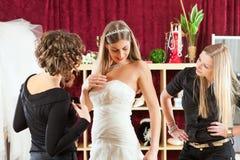 La mariée aux vêtements font des emplettes pour des robes de mariage Photographie stock libre de droits