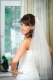 La mariée dans la robe de mariage a mis ses mains sur ses gratte-culs Photos stock