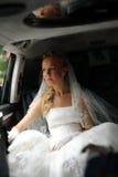 La mariée dans la robe de mariage s'assied dans la limousine image libre de droits