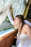 La mariée dans une robe blanche à un hublot Photographie stock libre de droits