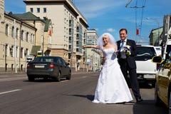 La mariée et le marié drôles attrapent le taxi sur la rue Photographie stock libre de droits