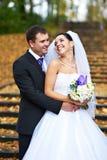 La mariée et le marié joyeux en automne jaune stationnent Photos libres de droits
