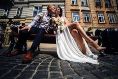 La mariée et le marié s'asseyent sur le banc Photographie stock libre de droits