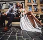 La mariée et le marié s'asseyent sur le banc Photographie stock