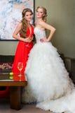 La mariée et sa demoiselle d'honneur avec une glace de vin Images libres de droits