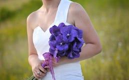 La mariée remet des fleurs de pourpre de fixation image stock