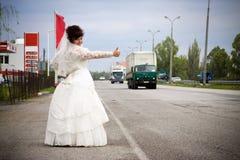 La mariée reste sur le bord de la route à côté de passer des véhicules Photographie stock