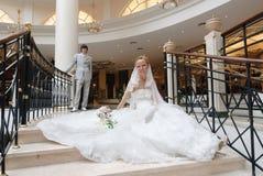La mariée s'assied sur l'escalier. Derrière elle est de retour le marié Image stock