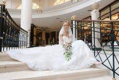 La mariée s'assied sur l'escalier spiralé large Photo stock