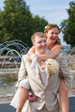La mariée s'assied sur un dos au marié Image libre de droits