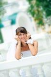 La mariée songeuse de sourires s'est penchée les coudes sur l'ha Image libre de droits
