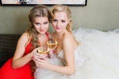 La mariée et sa demoiselle d'honneur avec une glace de vin Photo stock