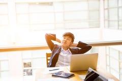 La marimacho corta del negocio del pelo negro del asiático se sienta delante de los wi del ordenador portátil Foto de archivo libre de regalías