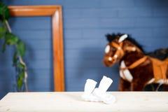 La marine, le mur bleu-foncé avec des vêtements de bébé et le cheval jouent Image stock