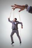 La marioneta del hombre de negocios que es manipulada por el jefe Fotografía de archivo
