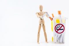 La marionnette en bois prennent les cigarettes aux décharges Backgr non-fumeurs de jour Images stock