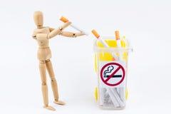 La marionnette en bois prennent les cigarettes aux décharges Backgr non-fumeurs de jour Photos libres de droits
