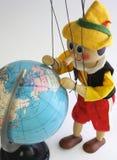 La marionnette en bois regarde le globe Photo stock