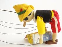 La marionnette en bois soulève des billets de banque Image stock