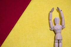 La marionnette en bois sur le feutre rouge et jaune d'acrylique de couleur supportent des bras photographie stock libre de droits