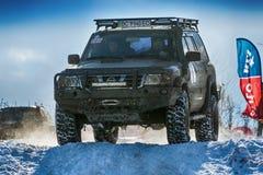 La marque tous terrains Nissan de véhicule surmonte la voie Image libre de droits