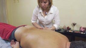 La masajista hace masaje remediador el lado izquierdo de nuevo a hombre gordo adulto Tiro medio almacen de video