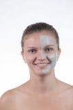 La maschera cosmetica di argilla grigia con sfrega sul fronte di giovane gir immagine stock libera da diritti