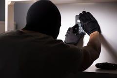 La maschera d'uso della passamontagna dello scassinatore alla scena del crimine Immagine Stock Libera da Diritti