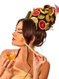 La maschera facciale del miele con la frutta fresca per capelli e la pelle sulla donna si dirigono Immagini Stock