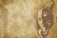 La maschera teatrale di carnevale sulla vecchia annata ha strutturato il fondo di carta Fotografie Stock