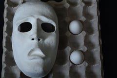 La maschera teatrale si trova nel contenitore dell'uovo con le uova del pollo Fotografia Stock Libera da Diritti