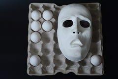 La maschera teatrale si trova nel contenitore dell'uovo con le uova del pollo Fotografie Stock Libere da Diritti