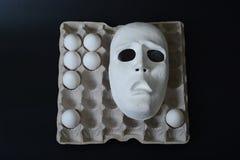 La maschera teatrale si trova nel contenitore dell'uovo con le uova del pollo Fotografia Stock