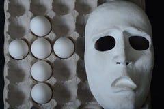 La maschera teatrale si trova nel contenitore dell'uovo con le uova del pollo Immagine Stock Libera da Diritti
