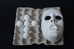 La maschera teatrale si trova nel contenitore dell'uovo con le uova del pollo Immagini Stock Libere da Diritti