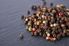La massa di vari semi dei granelli di pepe del pepe si mescola sulla pietra scura immagini stock libere da diritti