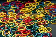 La masse des bandes élastiques rouges, bleues, jaunes et vertes. Photographie stock libre de droits