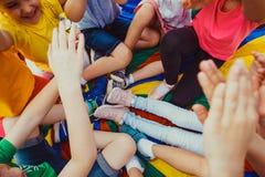La masse des jambes du ` s d'enfants sur un plancher coloré Photographie stock