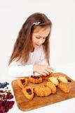 La materia de la niña se apelmaza con las bayas frescas Foto de archivo