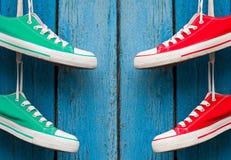 La materia textil se divierte los zapatos que cuelgan en una pared azul Fotografía de archivo