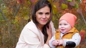 La maternidad y la niñez, el niño hermoso y la madre tienen un buen rato junto al aire libre en primer del parque de la ciudad de metrajes