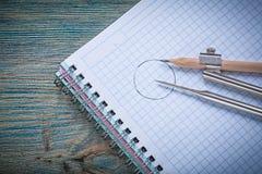 La matita d'annata della bussola di disegno ha controllato il quaderno sul bordo di legno co Fotografie Stock Libere da Diritti