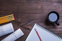 La matita del blocco note blueprints il metro e la tazza di caffè di legno sul pino Fotografie Stock
