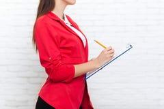 La matita della cartella della tenuta della donna di affari scrive il rivestimento di rosso di usura immagini stock