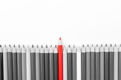 La matita rossa che sta fuori dalle matite monocromatiche ammucchia Fotografia Stock
