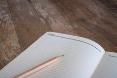 La matita sul taccuino sullo scrittorio non è vecchia Fotografia Stock