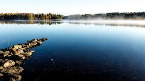 La mattina nebbiosa di autunno sul lago con dorato alleggerisce la nebbia fotografia stock