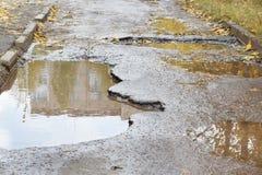 La mauvaise route goudronnée avec grands nids de poule remplis avec de l'eau Assiette de la route détruite dangereuse photo stock