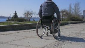 La mauvaise route pour le fauteuil roulant, fauteuil roulant de déplacement de difficulté sur la rue, handicapée fait le fauteuil banque de vidéos